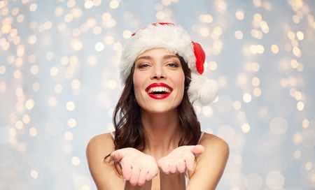 christmas and holidays concept - happy smiling young woman with empty hands in santa hat over festive lights background