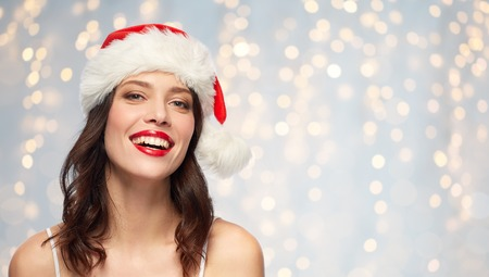 christmas and holidays concept - happy smiling young woman with red lipstick in santa hat over festive lights background Standard-Bild - 107815886