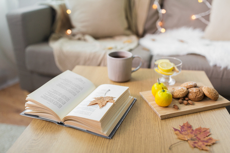 book, lemon, tea and cookies on table at home