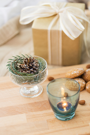 christmas fir decoration, candle, cookies and gift