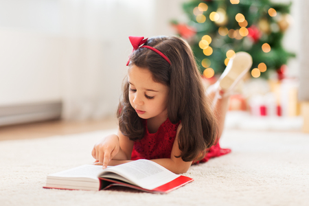 happy girl reading book at home on christmas Stock Photo