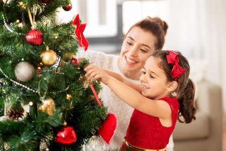 familia feliz decorando el árbol de navidad en casa Foto de archivo