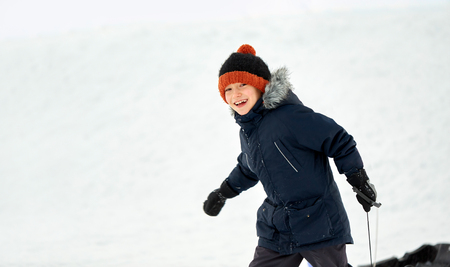 happy little boy with sled in winter outdoors Stock Photo