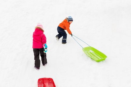 kids with sleds climbing snow hill in winter