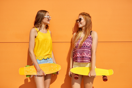 teenage girls with short skateboards outdoors Stock Photo
