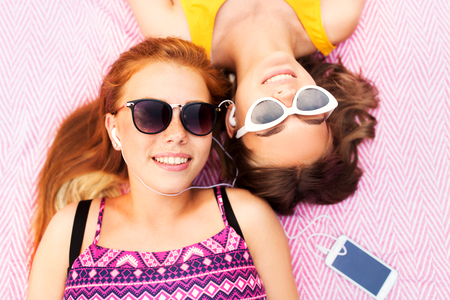 teenage girls listening to music from smartphone Stock Photo