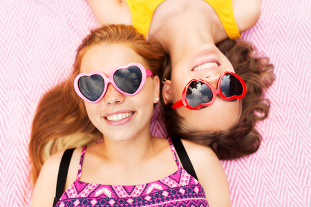 teenage girls in sunglasses on picnic blanket