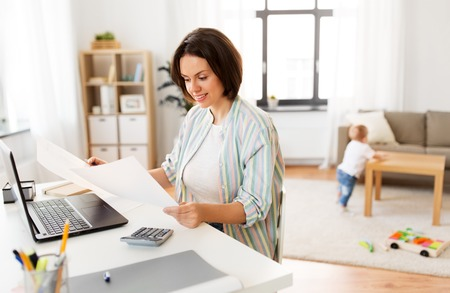 mother working with papers and baby boy at home Stock Photo