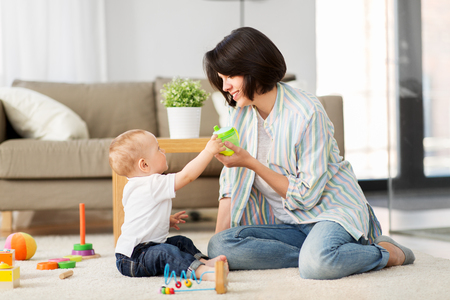 happy mother giving sippy cup to baby son at home Stock Photo