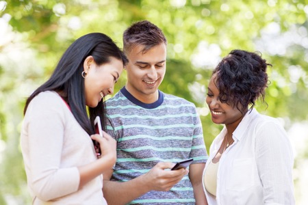 group of happy friends with smartphone outdoors Stock Photo