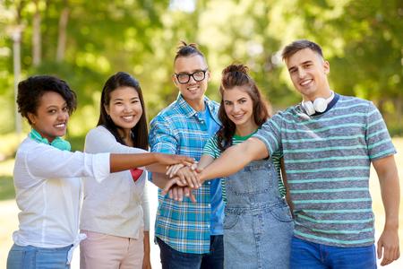 Amigos sonrientes felices apilando la mano en el parque Foto de archivo - 108117125