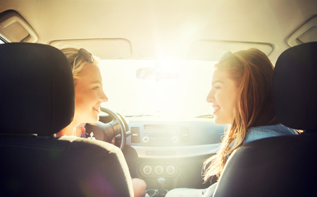 summer vacation, holidays, travel, road trip and people concept - happy teenage girls or young women driving in car Stock Photo