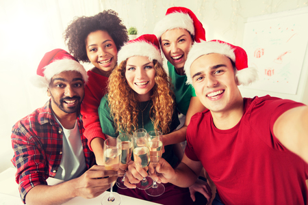 christmas, celebration and holidays concept - happy team in santa hats clinking glasses of non-alcoholic sparkling wine at corporate office party
