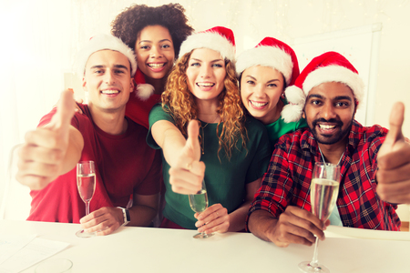 christmas, celebration and holidays concept - happy team in santa hats with non-alcoholic sparkling wine at corporate office party and showing thumbs up Stock Photo