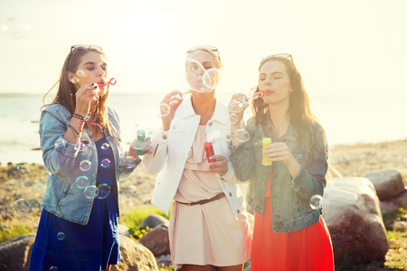 summer vacation, holidays, fun and people concept - group of happy young women or teenage girls blowing bubbles on beach Stock Photo