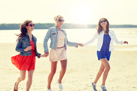 summer vacation, holidays, travel and people concept - group of smiling young women in sunglasses and casual clothes running along beach