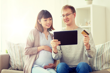 online shopping, pregnancy and people concept - happy husband and his pregnant wife with tablet pc computer and credit card at home
