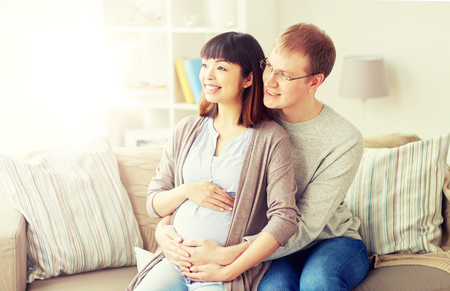 pregnancy, family and people concept - happy pregnant wife with husband sitting on sofa at home