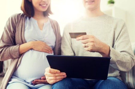 online shopping, pregnancy and people concept - close up of happy man and his pregnant wife with tablet pc computer and credit card at home