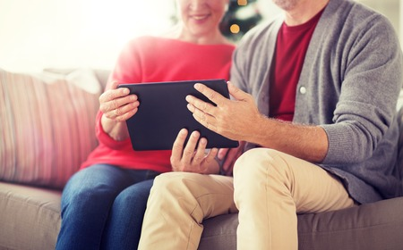 christmas, holidays and people concept - close up of happy smiling senior couple with tablet pc computer at home Stock Photo