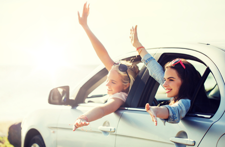 summer vacation, holidays, travel, road trip and people concept - happy teenage girls or young women in car at seaside waving hands