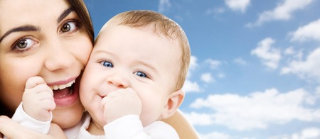 family and motherhood concept - happy smiling young mother with little baby over sky background