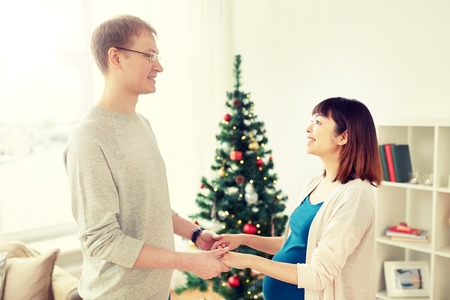 pregnancy, winter holidays and people concept - happy pregnant wife with husband at home at christmas