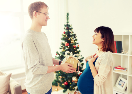 pregnancy, winter holidays and people concept - happy husband giving christmas present to his pregnant wife at home Stock Photo