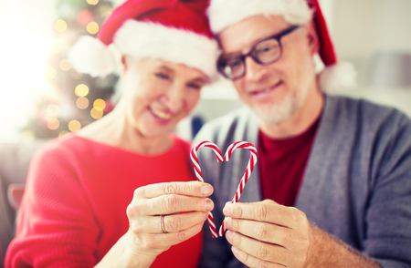 christmas, holidays and people concept - close up of happy smiling senior couple in santa hats with heart of candy canes at home Stock Photo