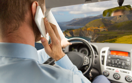 business trip, technology and social issue concept - close up of businessman calling on smartphone and driving car over bixby creek bridge on big sur coast of california background Stock Photo