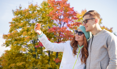 technology, people and season concept - smiling couple with smartphone taking selfie over autumn park background