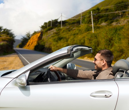 road trip, travel and people concept - happy man driving convertible car over road and big sur hills background in california