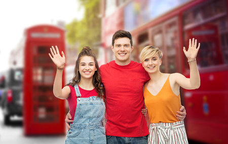 travel, tourism and summer holidays concept - group of happy smiling friends hugging over london city street background