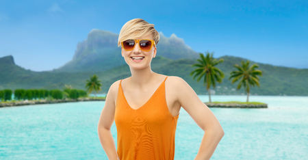 travel, tourism and summer holidays concept - happy smiling teenage girl in sunglasses at touristic resort over bora bora island beach background