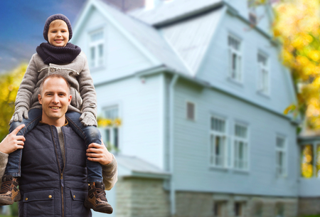family, real estate and fatherhood concept - happy father carrying son over living house background