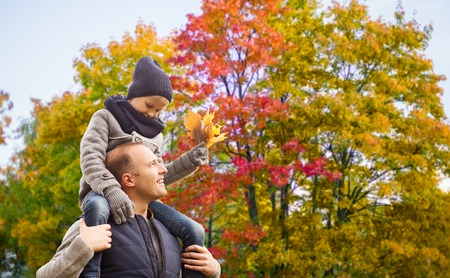 family, childhood and fatherhood concept - happy father carrying son with maple leaves over autumn park background
