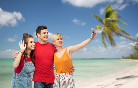 travel, tourism and summer holidays concept - group of happy smiling friends taking selfie by smartphone and hugging over exotic tropical beach with palm trees background