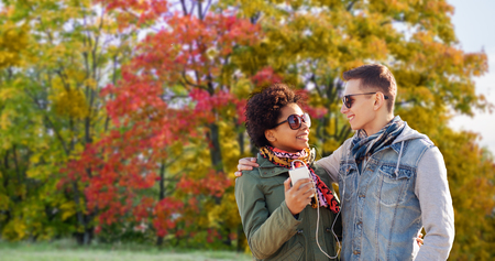 technology, relationships and season concept - smiling mixed race couple with smartphone and earphones listening to music over autumn park background