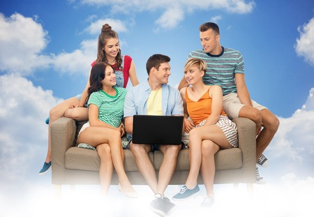 friendship, leisure and technology concept - group of happy smiling friends with laptop computer sitting on sofa over blue sky and clouds background Stock Photo