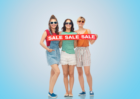 shopping and people concept - happy smiling teenage girls with sale banner over blue background