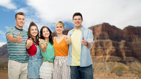travel, tourism and summer holidays concept - group of happy smiling friends showing thumbs up over grand canyon national park background