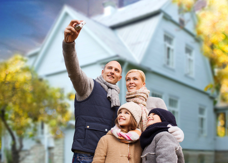 family takes autumn selfie by camera over house