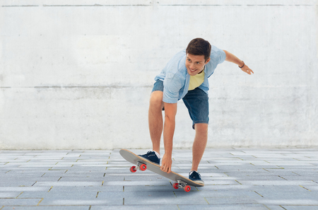 young man riding skateboard over urban background