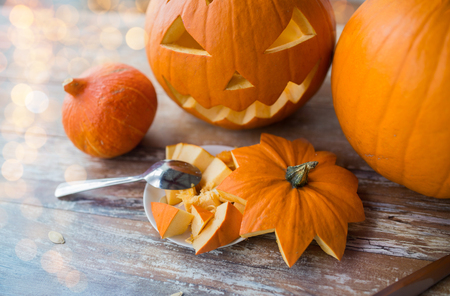 halloween, holidays and decoration concept - jack-o-lantern or carved pumpkin on wooden table with spoon at home