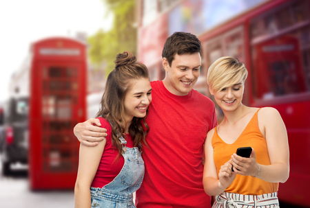 friends with smartphone over london city street