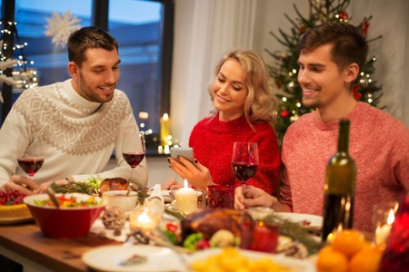 friends with cellphone celebrate christmas at home