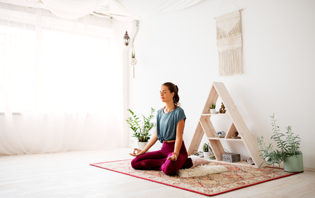 woman meditating in lotus pose at yoga studio