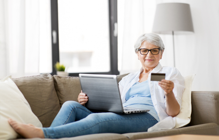 senior woman with laptop and credit card at home Stock Photo