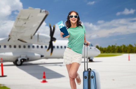 tourism, summer holidays and vacation concept - happy teenage girl in sunglasses with travel bag and air ticket over plane on airfield background