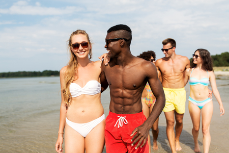 mixed race couple walking along beach with friends